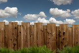 brauner Holzzaun im Garten bei blauem Himmel mit Wolken - 186423840