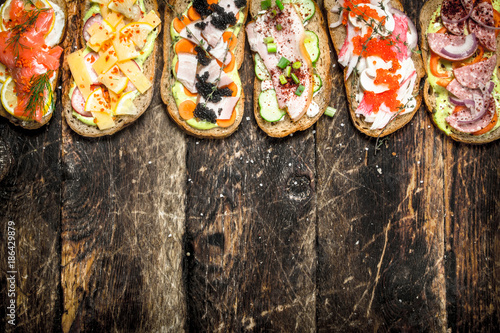 Sandwiches with salmon, cheese, mushrooms and fresh vegetables. - 186429879