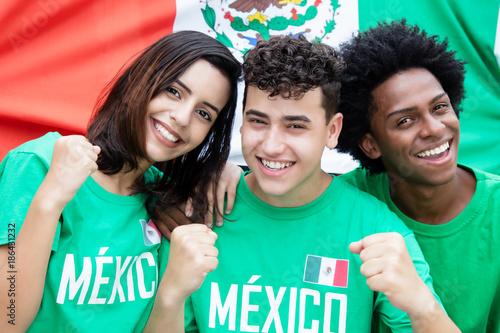 canvas print picture Drei lachende mexikanische Fussball Fans mit Fahne