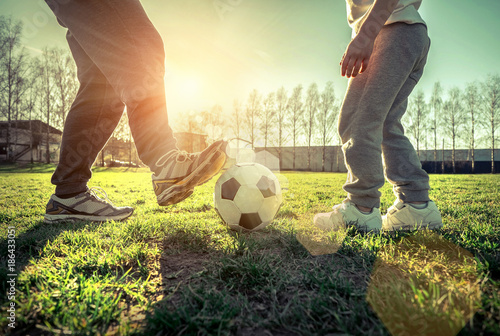 Fotobehang Voetbal Father and son playing together with ball in football under sun