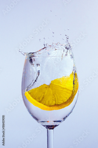 A slice of lemon falls into the glass with vodka. Bubbles and splashes appear