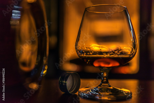 Time to enjoy! A glass filled with cognac stands on a table next to a cognac bottle. In the background a fireplace. Focus is on the bottle cap. Concept: drink or health