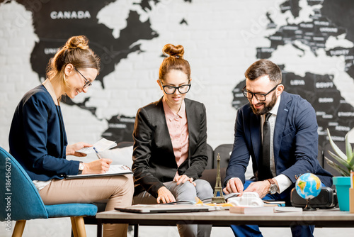 Young businesscouple choosing a trip with agent sitting at the travel agency office with world map on the background