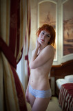 Red-haired girl with short red hair posing nude in hotel room