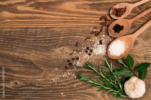 Tavola con mestoli, sale e erbe aromatiche