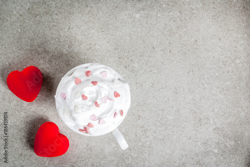 Fotobehang Chocolade Romantic background, Valentine's day. Cup for coffee or hot chocolate, with whipped cream and sweet hearts, with two plush red hearts, copy space top view
