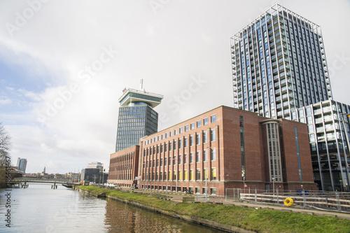 Foto op Aluminium Amsterdam Vista di cue palazzi di recente costruzione nella parte nord di Amsterdam, in Olanda. Un palazzo basso in mattoncini sta davanti ad un grattacielo.