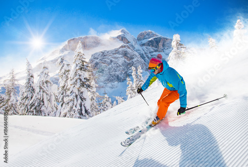 Skier skiing downhill in high mountains - 186464885