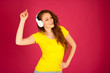 Beautiful young woman listen to the music over vibrant color background