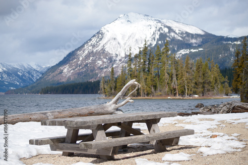 Picnic tables on winter beach of mountain lake
