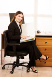 Young business woman with bold folder checking data at her desk in the office - 186478893
