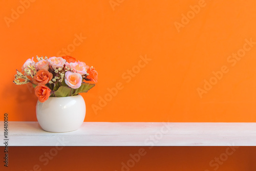 Orange wall with flowers on shelf white wood, copy space for text. Still life Concept