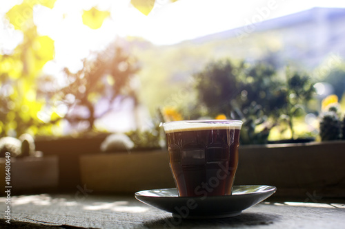 Papiers peints Cafe Glass of hot Americano with steaming on a wooden table in the cafe with bokeh tree garden background, black coffee.