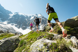 Three trail runners, two men and a woman, running up a steep trail in the mountains in the Alps on a hot, bright summer day. - 186488201