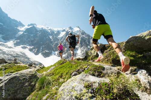 Fototapeta Three trail runners, two men and a woman, running up a steep trail in the mountains in the Alps on a hot, bright summer day.