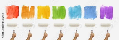 hand with roller paint on wall with colors samples, banner web template