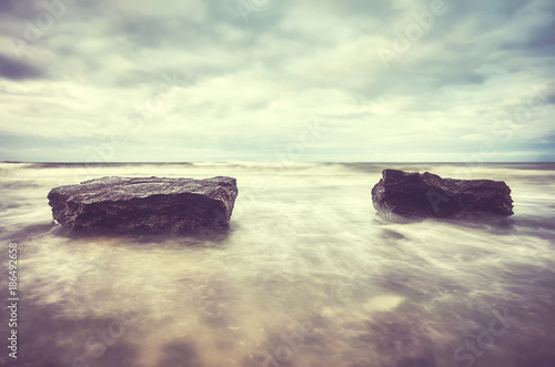 Foto op Canvas Natuur Two rocks on a beach, motion blurred water, peaceful natural background, color toned picture.