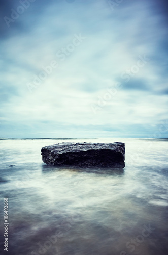Foto op Canvas Natuur Stone on a beach, motion blurred water peaceful natural background, color toned picture, selective focus.