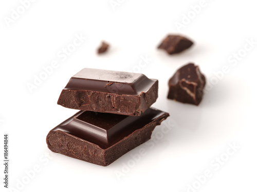 Macro photo of Chocolate bar. Broken pieces over white background