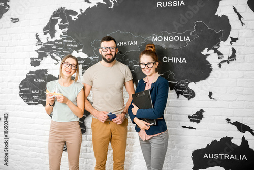 Foto Murales Portrait of a young couple of travelers choosing a summer strip standing with travel agent on the world map background