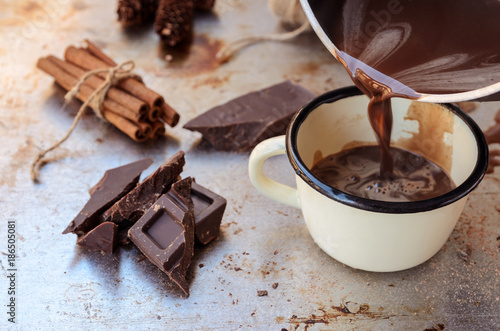 Foto op Canvas Chocolade Hot chocolate poured from pot into metal mug cup. Winter times drink background with copy space.. Delicious cold weather beverage concept.