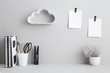 Creative desk with blank picture frame or poster, desk objects, office supplies, books and plant on a gray background. Creative desk.
