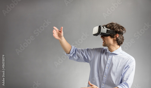 Foto Murales Young man playing in virtual reality goggles