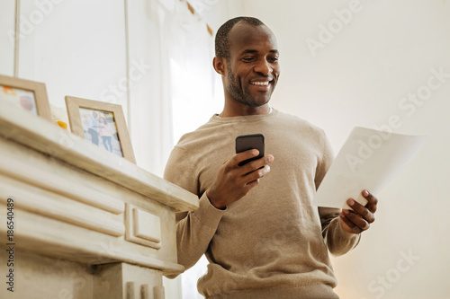 Happy day. Cheerful bearded afro-american man laughing and holding his phone while standing near the shelf with photos and looking at the sheet of paper