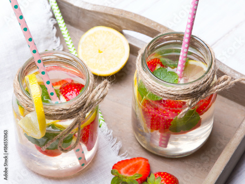 Foto Murales Mineral  water with fresh strawberries, lemon  and mint in jar on a white wooden background, copy space