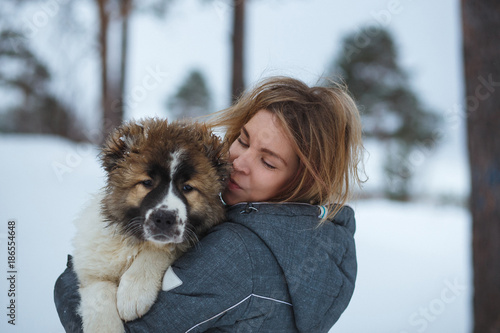 Portrait Girl with cute Caucasian Shepherd Dog in winter park Poster