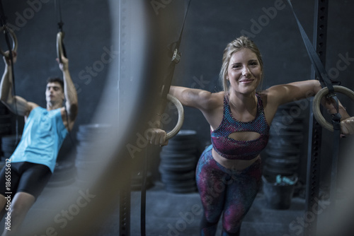 Woman training with rings in crossfit room