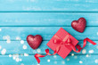 Gift and red heart on turquoise wooden background top view. Saint valentine day greeting card.