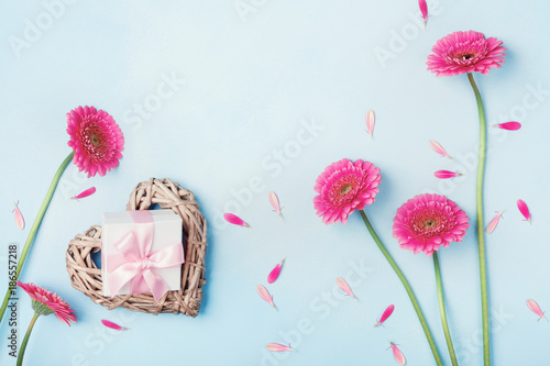 Fotobehang Gerbera Spring background with flowers, heart and gift box on blue table top view. Greeting card for Birthday, Woman or Mothers Day. Flat lay.