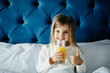 Beautiful girl girl holding glass of orange juice, showing thumb up gesture, looking at camera while sitting in bed