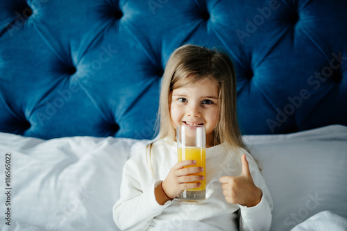 Beautiful girl girl holding glass of orange juice, showing thumb up gesture, looking at camera while sitting in bed - 186565022