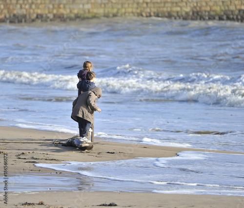 Enfants qui jouent avec l'écume de mer. - 186566872