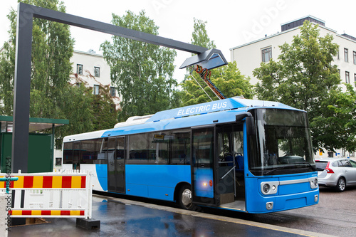 Fototapeta Electric bus at a stop is charged by pantograph