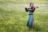 Beautiful female viola player on a wildflower meadow - 186569076