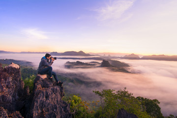 Photographer sit on top of the hill and taking landscape photo