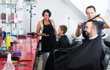 Glad female hairdresser cutting male client - 186577456