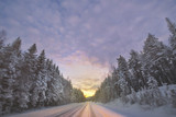 Winterroad in spruce forest at sunrise during a very clear cold morning