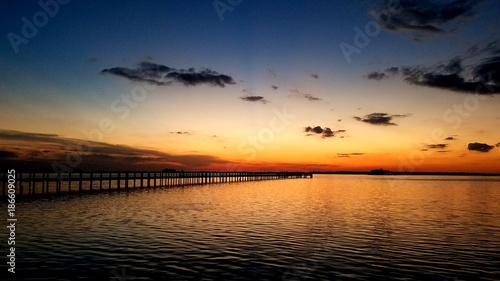 Scattrered dark clouds with orange horizon after sunset over a fishing pier  - 186609025