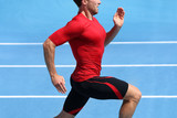 Athlete runner running on athletic track training cardio. Jogger man jogging fast pace for competition race on blue outdoor stadium tracks wearing red compression sport clothes. Male person fit body. - 186622098