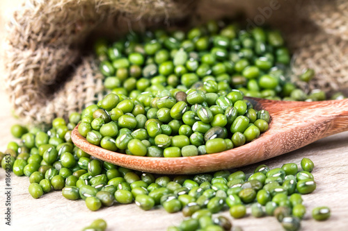 close up green mung beans in wooden spoon on wood plate - 186623453