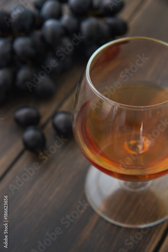 A wineglass of brandy or cognac with a bunch of black grapes