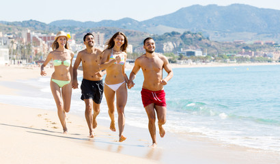 Happy people running at beach