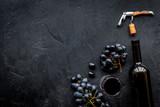 Open the wine. Corkscrew near bottle on black background top view copyspace - 186636683
