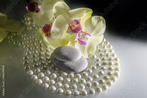 Tuinposter Spa flat stones on a white glass on the background of yellow orchids