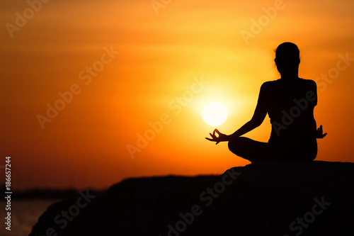 Fotobehang Oranje eclat Silhouette of young asian woman practicing yoga on the beach at sunset.relaxing concept.