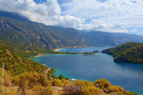 Amazing aerial view of Blue Lagoon in Oludeniz, Turkey. Summer landscape with mountains, green forest, azure water, sandy beach and blue sky in bright sunny day. Travel background. Top view. Nature - 186668462